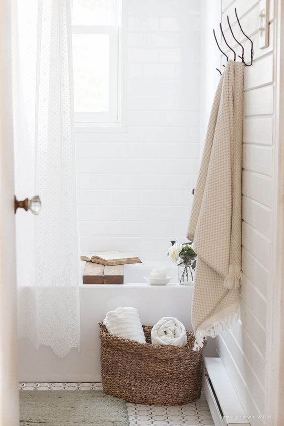 crisp white shower curtains woven baskets for towels hanging pastel towel white tile walls built in bathtub in white