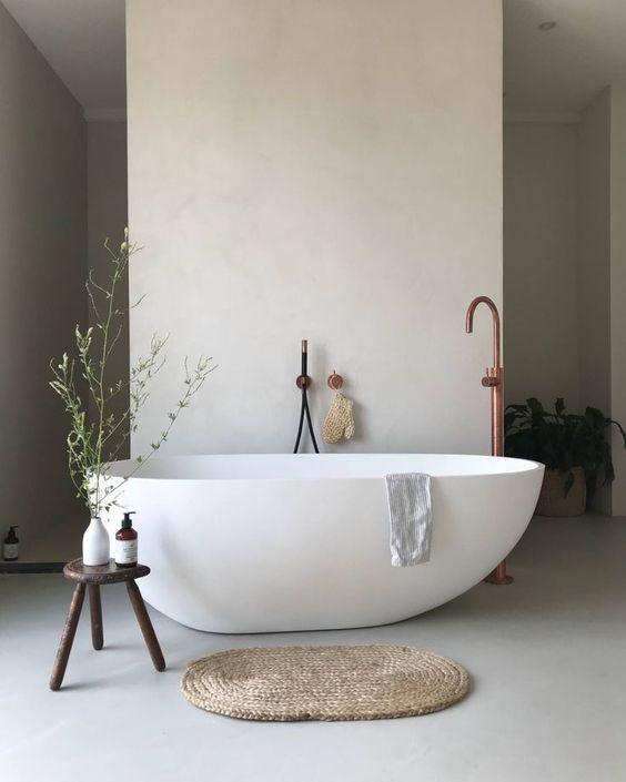 crisp white tub flat woven bath mat small wooden stool free standing bath faucet in bronze