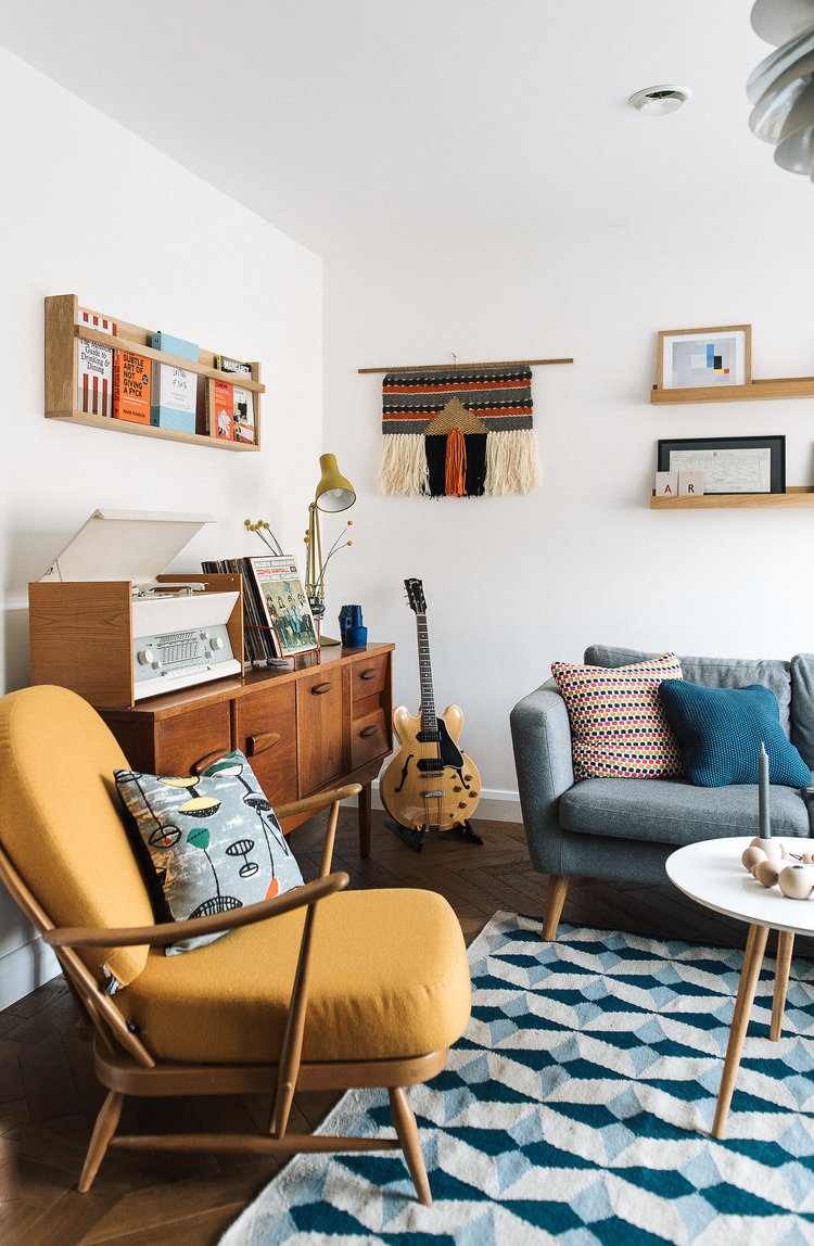 crisp white walls bold yellow armchair blue loveseat with colorful throw pillows light bold blue area rug with geometric patterns wooden cabinets