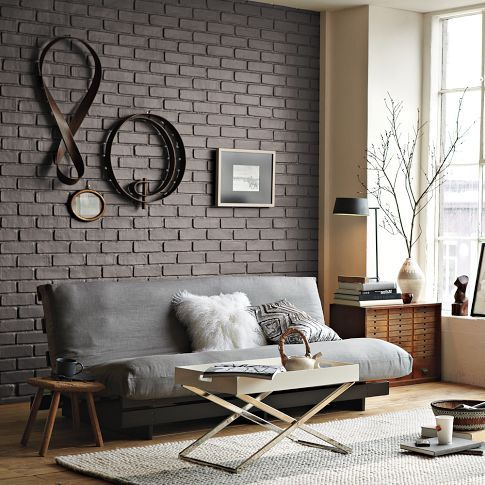 deep gray brick wall with some wall decors soft gray sofa wood side table dark wood console x base brass table tray knitted area rug in white color