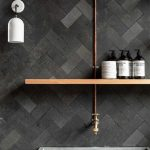 Herringbone Tile Wall In Black Open Wooden Shelf Brass Finish Piping Wall Sconce In White Bare Concrete Tub In Square Shape