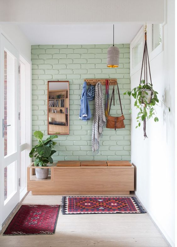 light green brick accent wall wooden cabinet with seat Boho mats hanging greenery on pot wall mirror