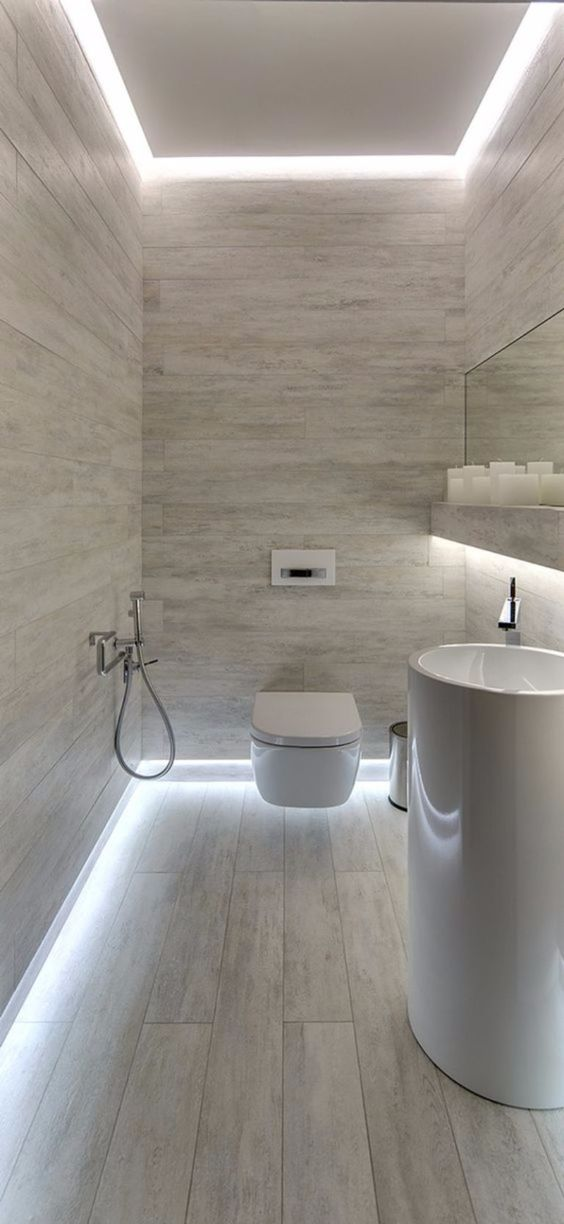 light toned bathroom interior wall mounted toilet in white tall bathroom sink in white