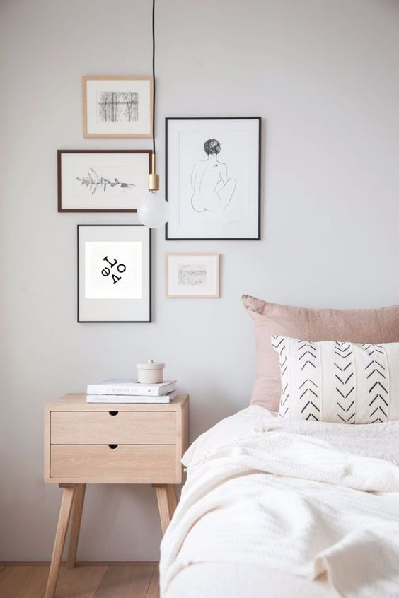 light wood nightstand a cluster of framed wall arts simple modern pendant in low profile white bedding treatment