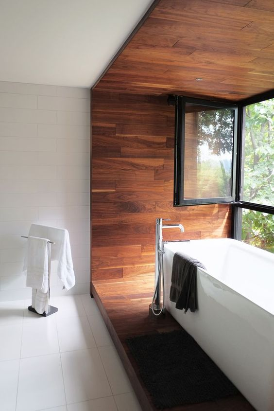 minimalist bathroom design with modern white bathtub free standing faucet wood accent walls and floors glass windows with black trims white tile walls and floors