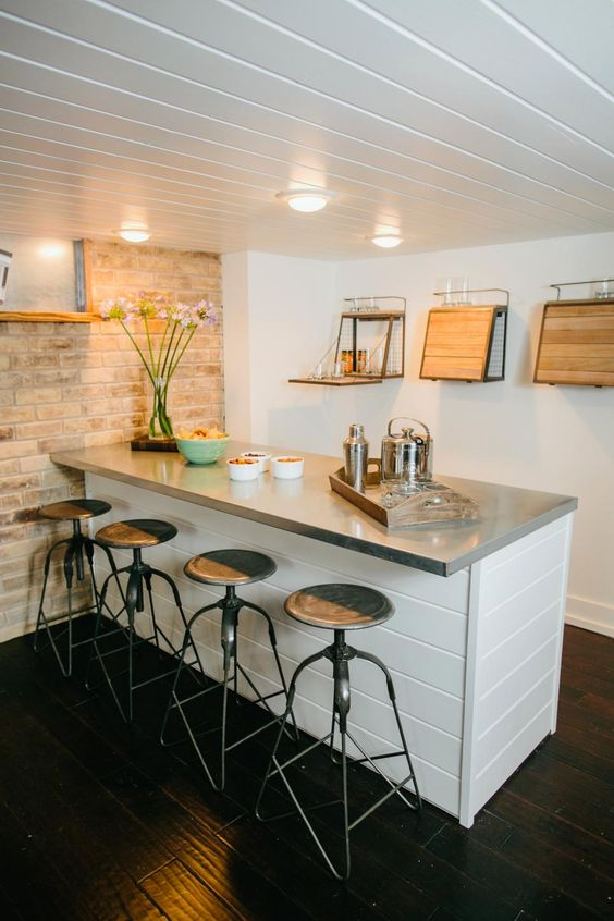 modern coastal home bar idea white counter with gray countertop round top bar stools with black iron legs washed brick walls crisp white walls with unique wooden storage