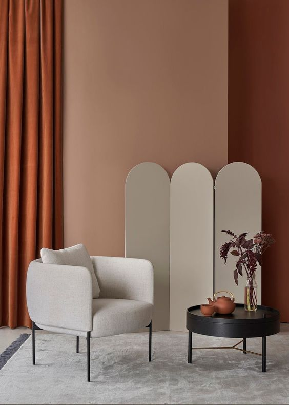 modern white armchair round top coffee table in black light pink natural brown walls terracotta draperies