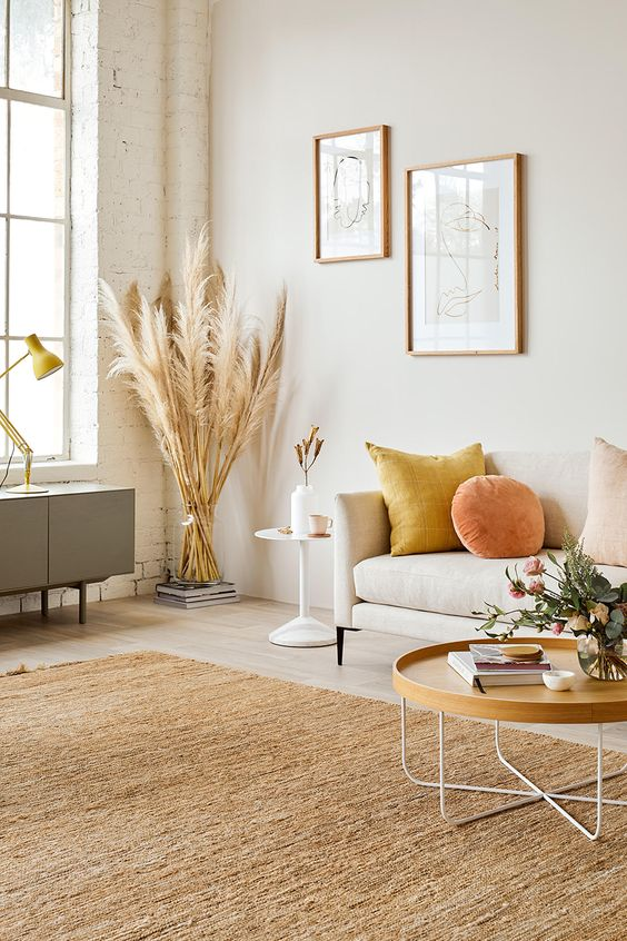 pampas grass in the corner crisp white sofa colorful throw pillows light wood color coffee table with white wire legs textured brown area rug