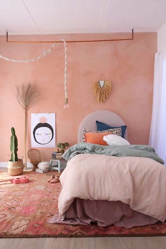 pink wall white ceilings layered duvet covers in different colors earthy brown area rug with motifs woven pot with cactus accent pendant