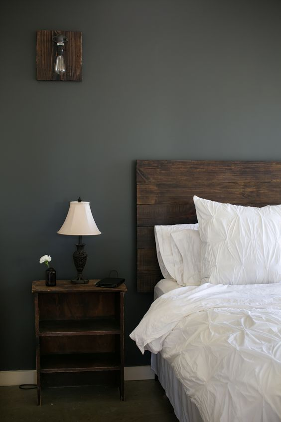 reclaimed wood headboard and nightstand crisp white cotton duvet and shams dark gray walls wall sconce with reclaimed wood stand