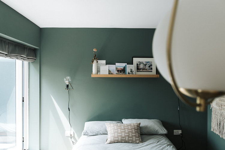 smoke green walls wood open shelf for frames and vase white bed linen and pillows gray draperies white macrame wall decor