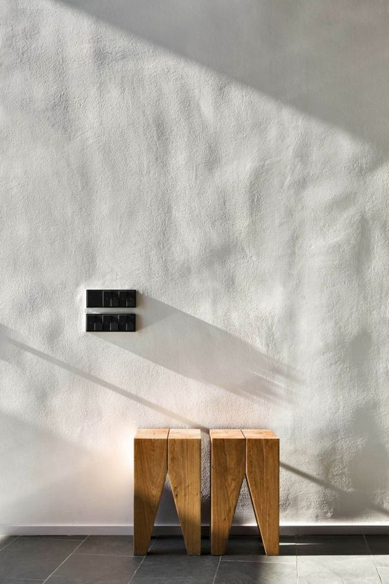 smooth texture concrete wall in clean white a couple of wooden stools