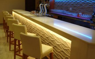 superlarge and fancy home bar design longer counter in white with under shiny panel modern white bar stools wooden shelves with textured and lighted wall background