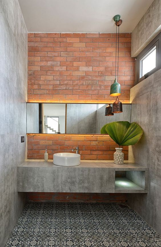 vintage tile floors concrete wall and bathroom vanity round shaped sink in white potted houseplant red brick wall frameless wall mirror