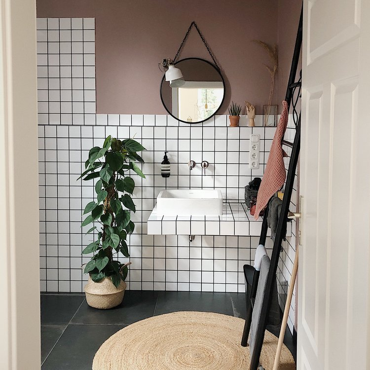 white ceramic tile walls and smoke pink wall floating vanity's counter with white traditional sink natural fiber pot with houseplant black ladder rack round woven rug