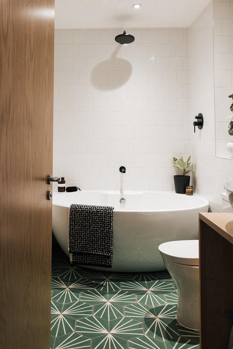 white ceramic tile walls modern white bathtub smoke green tile floors with white geometric patterns