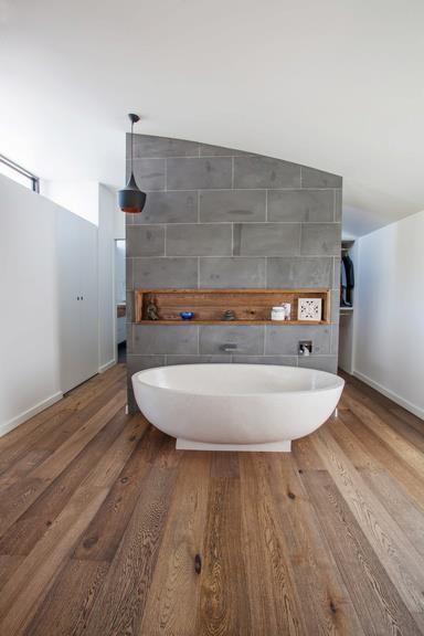 white tub recessed wood shelf concrete wall partition organic wood floors