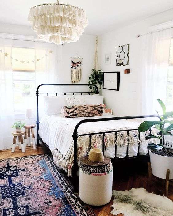 Boho chandelier in white classic black metal bed frame with headboard and footboard multicolored area rug cowhide area rug