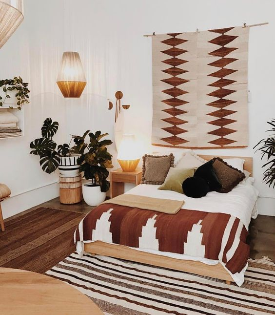 Boho farmhouse bedroom artsy wall decor with geometric patterns striped area rug big houseplants on big planters