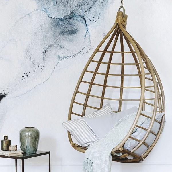 Broste hanging chair made from rattan with some throw pillows and blanket