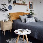 Scandinavian Style Guest Bedroom Bed Frame With Solid Wood Headboard Lightwood Nightstand White Round Top Side Table With Angled Wood Legs Small Runner With Modern Motifs Dark Blue Bed Linen