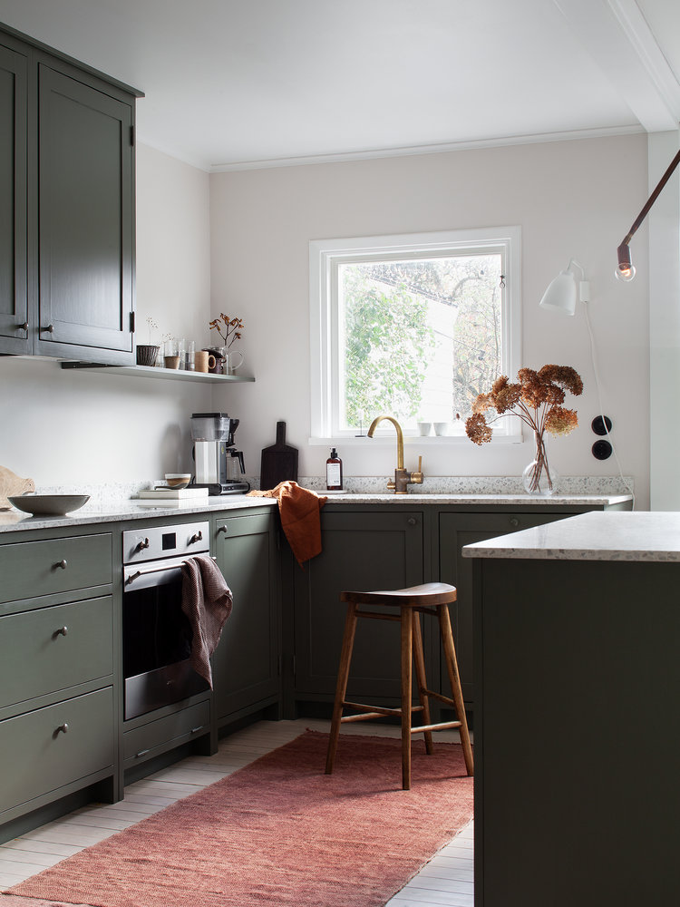 airy kitchen with medium size glass window gray kitchen cabinets white countertop dusty pink runner wooden stool