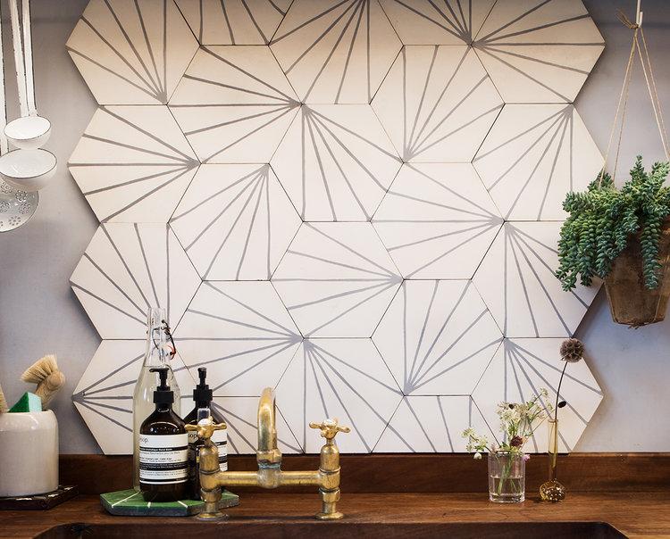 artsy backsplash tile installation with simple black line accents