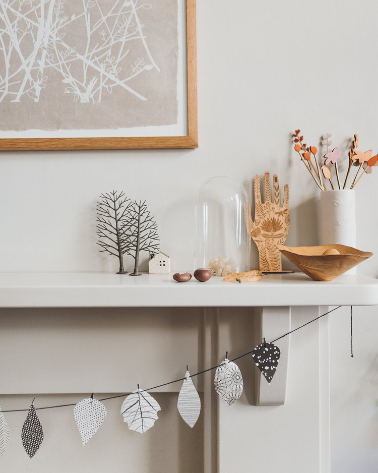 artsy display consisting of creative hand shaped art with neutral wrapping paper white vase with artificial flowers simple string of paper leaves in monochromatic scheme