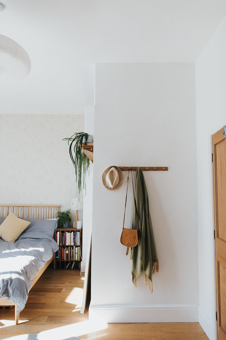 bright and airy bedroom simple wooden bed frame with headboard naturally blue bedding wooden bedside table with bookshelf underneath wooden cloth hanger