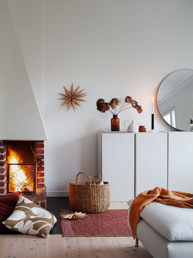 clean and bright interior with crisp white walls white cabinets frameless round mirror fireplace light wood floors modern white chaise with throw blanket pink runner some floor pillows