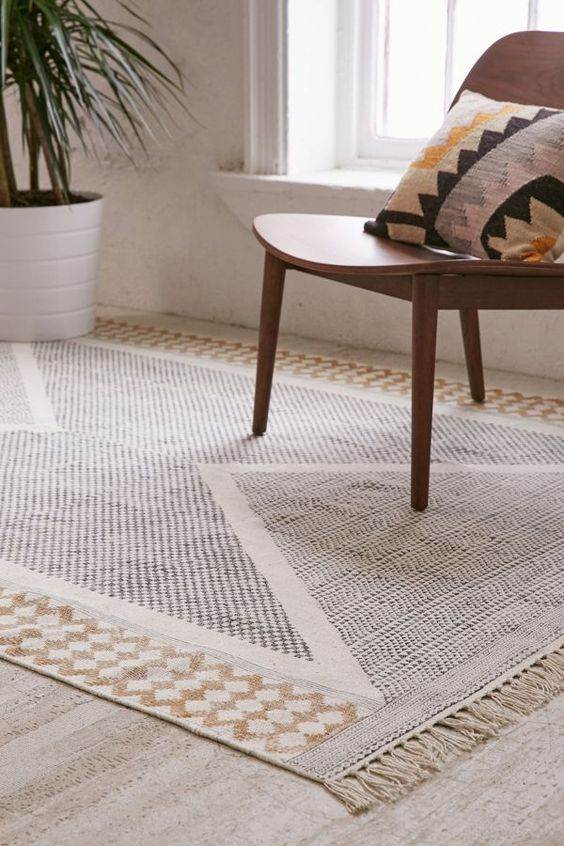 connected wool area rug with modern geometric patterns wooden chair in midcentury modern style multicolored throw pillow light wood floors