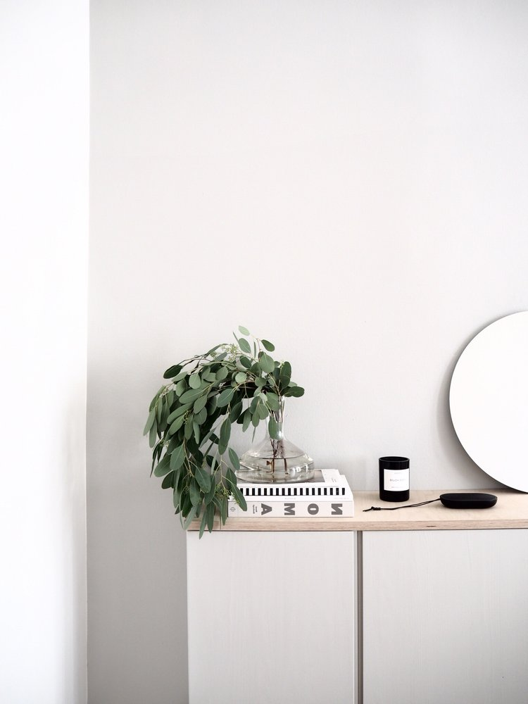 console table with light wood top frameless mirror in round shape greenery on glass vase