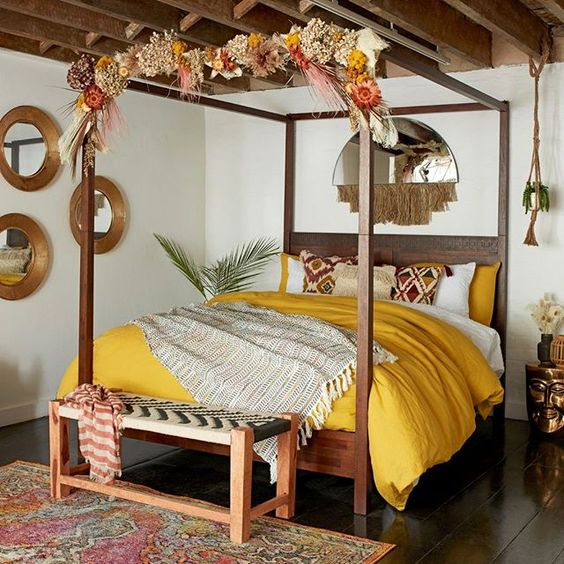 dark wood bed frame with canopy wooden bench bed multicolored rug framed wall mirrors in round shape half circle wall mirror with tassels pop of yellow duvet cover