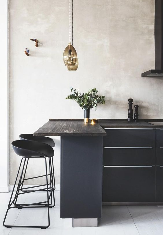 elegant black kitchen idea purely black cabinetry with metal accents modern black stools blackwashed countertop and bar table artsy pendants
