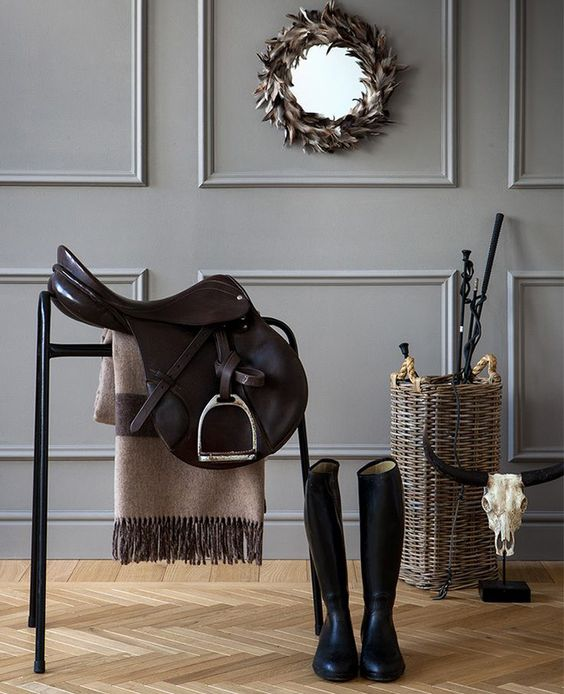 entryway with herringbone wood floors wainscotting wall panels in gray round wall mirror with wreath frame woven basket for storage