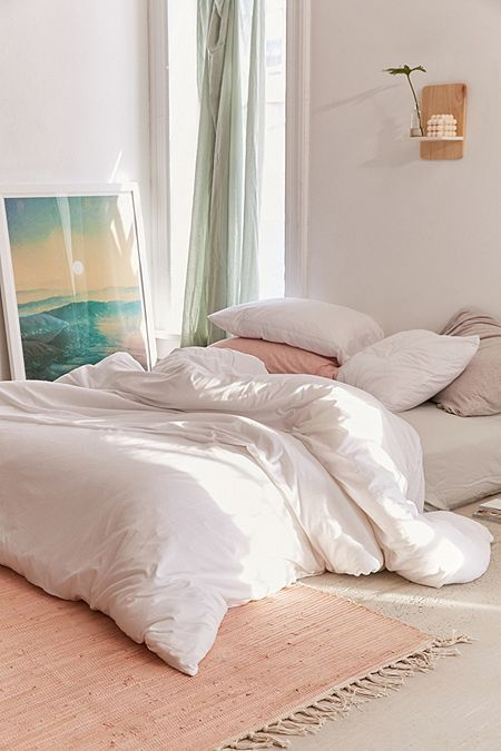 floor bed idea with white duvet cover and pillows peach pillows peach area rug with fringed trims