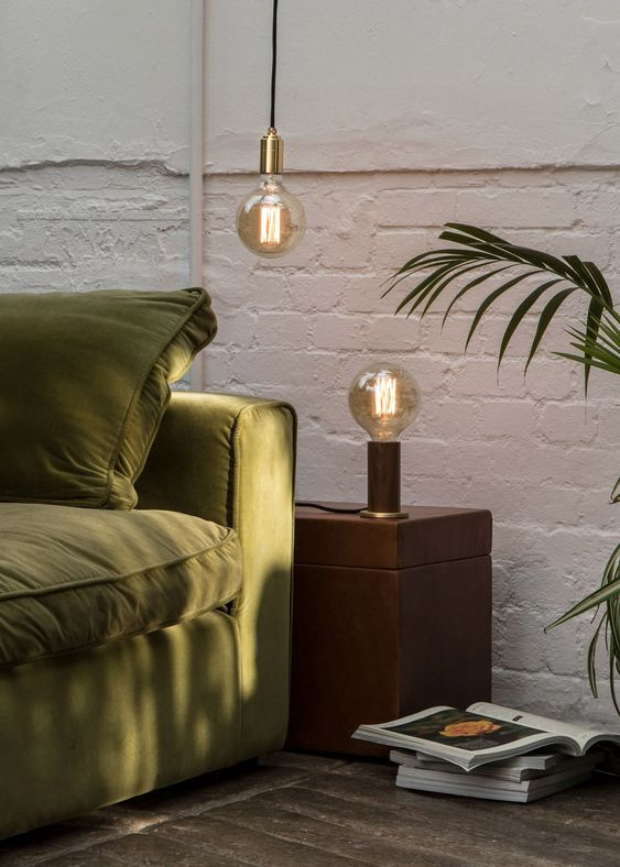 green olive sofa dark wood bedside table white walls accent light fixtures