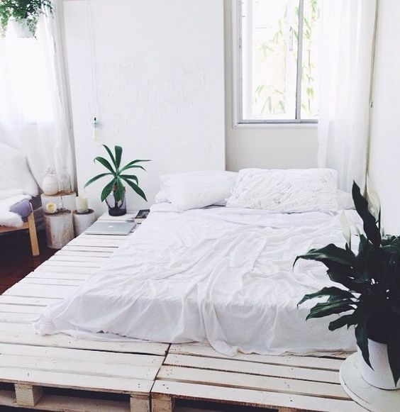huge platform bed frame with potted houseplants and mattress with crisp white bedding treatment