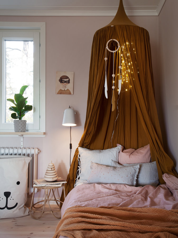 kid's bed frame with canopy and draperies light pink bed linen dusty pink duvet cover light blue pillows small rattan bedside table