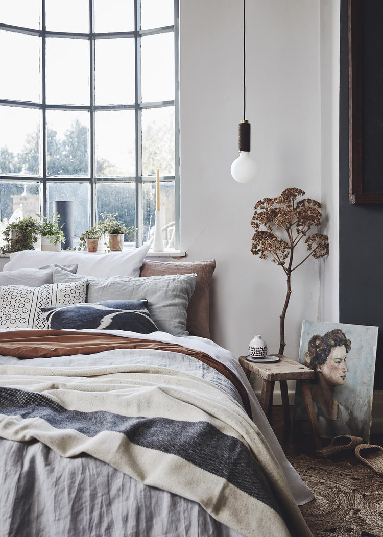 layered bedding treatment in neutral shades glass window with trims long wired pendant wooden side table