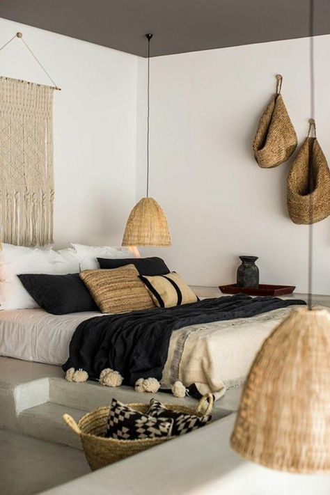 light and minimalist bedroom white bed linen black duvet cover with big pompoms macrame wall decor rattan wall decors accent light fixtures with oversized rattan lampshades