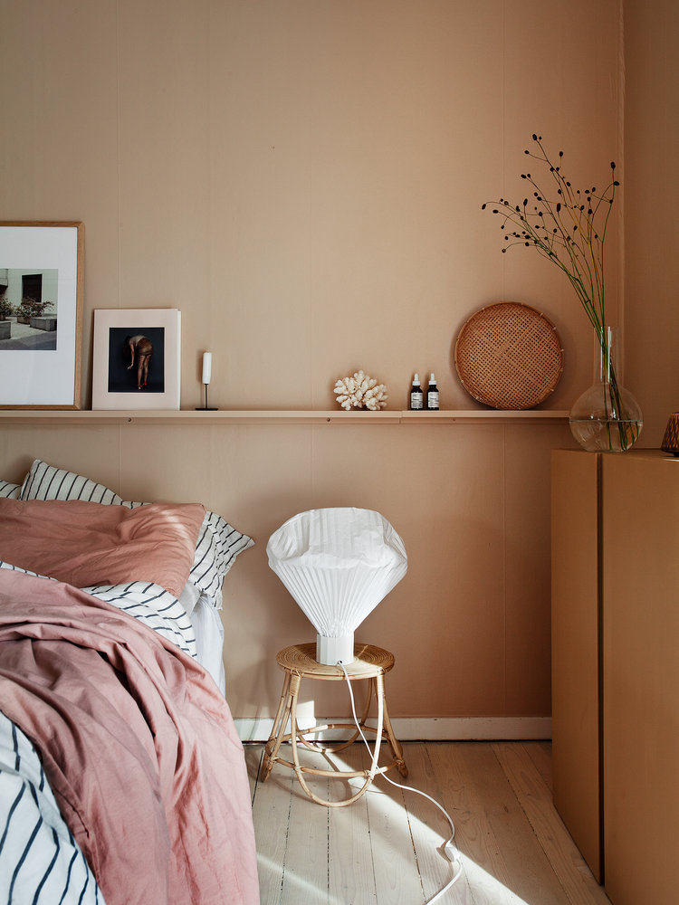 light pink walls single shelving unit for ornate frames and some accessories striped bed linen and pillows pink throw blanket round top bedside table light wood floors