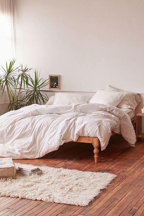 lightweight duvet cover in white white pillows white linen bedspread wooden bed frame white shag rug runner