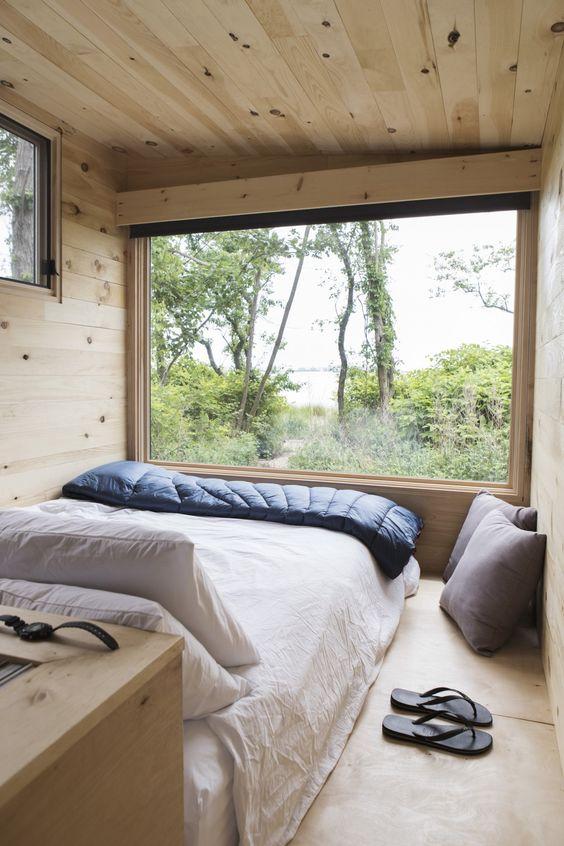 minimalist treehouse bedroom white bedspread navy blue comforter light wood interior glass window