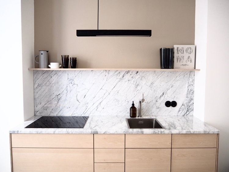 minimalist warm kitchen idea tan painted wall marble backsplash and countertop electric stove square sink and stainless faucet light wood cabinets