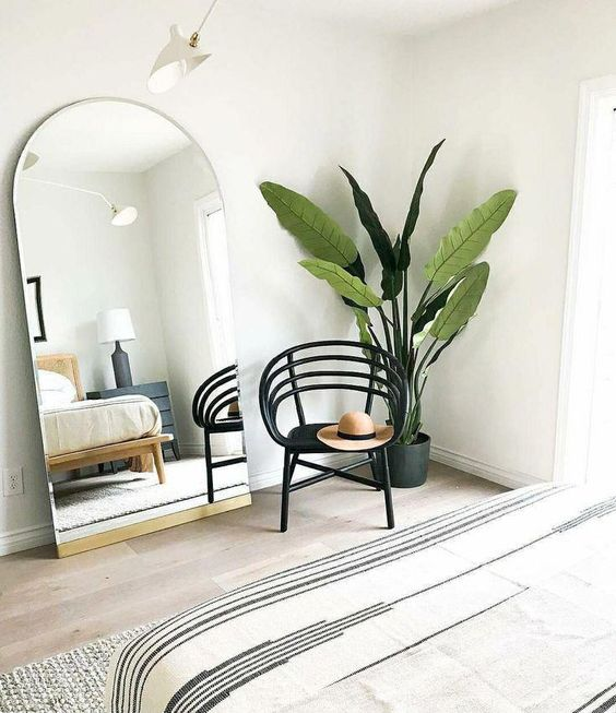 modern Boho bedroom idea houseplant with black planter black chair frameless mirror light wood floors white walls
