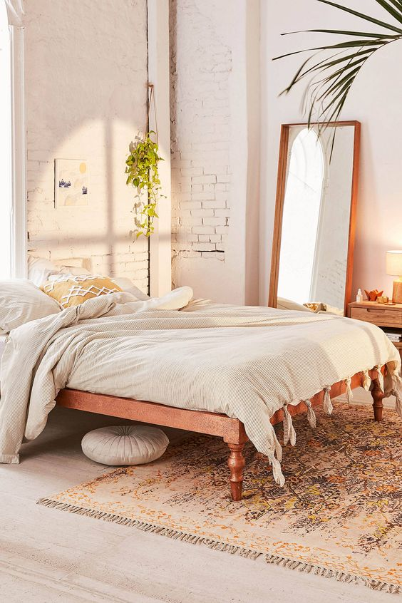 modern Boho bedroom with multicolored rug dusty white duvet cover with tassels wood framed mirror and some houseplants