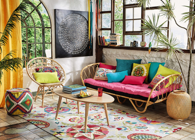 rattan daybed with pink cushion and colorful accent pillows rattan chair with colorful accent pillows colorful area rug pouf with colorful geometric patterns
