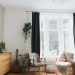 Small Sitting Area With Glass Window Dark Curtains Hanging Greenery Wood Floors Light Blue Area Rug In Round Shape