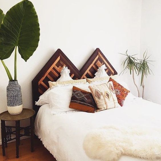unique reclaimed wood headboard with pointed tops white bedding treatment tribal pillows Moroccan bedside table with round top houseplant with porcelain vase
